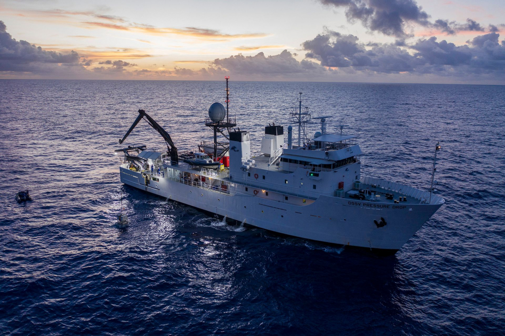 Tàu mẹ Pressure Drop thả neo tại tây bắc Thái Bình Dương, bên dưới là rãnh Mariana, nơi được biết là vực sâu nhất thế giới.