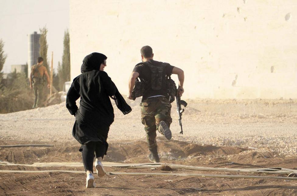 a woman reporter runs with a rebel fighter