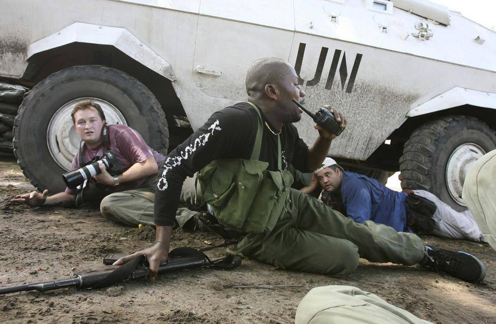 reuters congo correspondent david lewis l takes cover under a u n armored car during machine gun and mortar fire in kinshasa november 11 2006