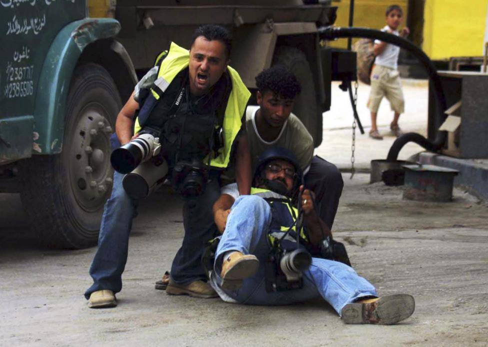 reuters palestinian photographer abed omar qusini c falls to the ground after being injured during clashes in the west bank city of nablus may 3 2004