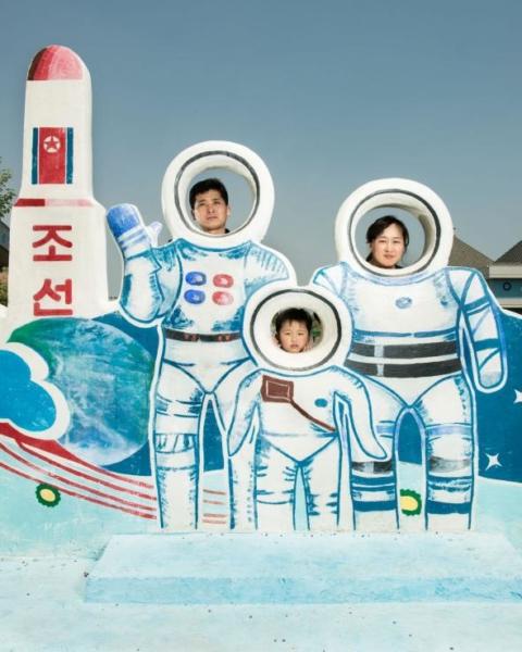 Một gia đình đứng đằng sau bức họa dùng để chụp ảnh lưu niệm, bức tranh mang chủ đề về chương trình không gian của Triều Tiên, được đặt tại một công viên nước trong thủ đô Bình Nhưỡng.