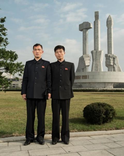 Hai nhân viên văn phòng đang đứng trước Đài tưởng niệm Thành lập Đảng Lao động Triều Tiên ở Bình Nhưỡng. Búa, lưỡi liềm và bút lông đại diện cho tầng lớp công nhân, nông dân và trí thức.