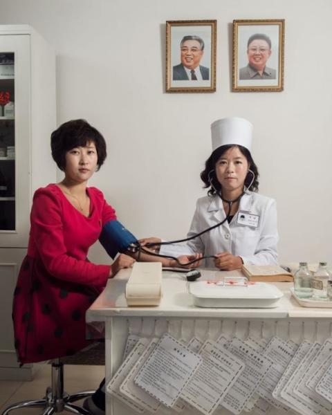 Một bác sĩ đang khám bệnh cho một công nhân tại nhà máy dệt may lớn nhất Triều Tiên, nơi mà phần lớn trong số 10.000 người làm việc là phụ nữ. Trước khi lệnh trừng phạt của Liên Hiệp Quốc được đưa ra vào năm 2017, hàng dệt may là một trong những mặt hàng xuất khẩu thế mạnh của quốc gia này.
