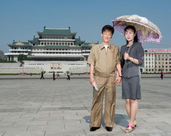 Một cặp vợ chồng đang đứng giữa Quảng trường Kim Nhật Thành, nơi đây có sức chứa 100.000 người và thường được tổ chức các cuộc diễu hành quốc gia. Tòa nhà phía sau họ là Đại học Tập đường Nhân Dân, một giảng đường đại học và thư viện lớn.