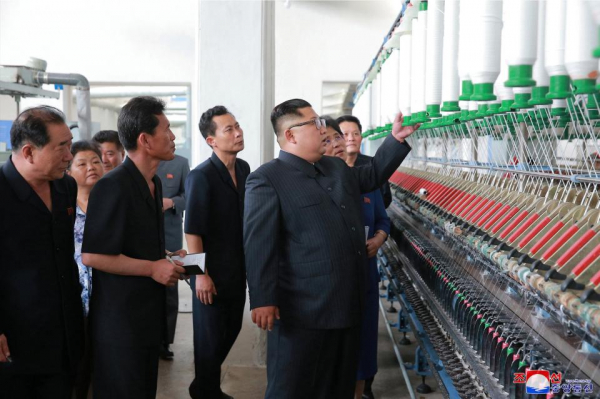 kim inspects machinery at a textile factory in sinuiju as anxious bosses look on as