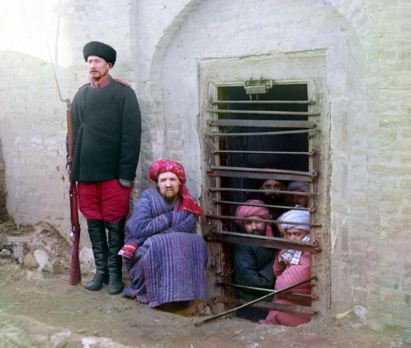 Những tù nhân nhìn ra ngoài từ sau song sắt tại một nhà tù thuộc lãnh thổ Trung Á của Nga, trong khi người gác ngục mặc đồng phục trang trọng đang đứng ở bên cạnh, chụp năm 1910.