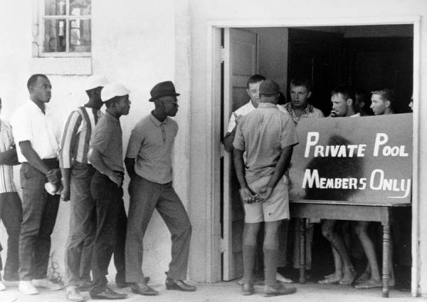 white men preventing black men from entering a pool