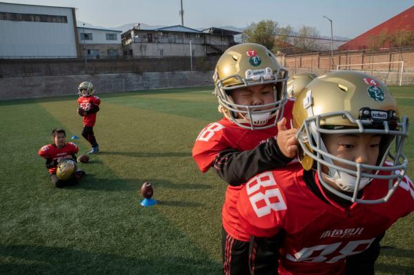 Sau khi được tìm hiểu về luật chơi và cách chơi, các cậu bé mặc đồng phục và bắt đầu một hiệp đấu bóng bầu dục – môn thể thao còn rất xa lạ với người Trung Quốc. Vào những buổi sáng tháng 12 lạnh lẽo, các cậu bé phải cởi áo và chạy bộ mình trần. Ảnh: Gilles Sabrié/The New York Times.