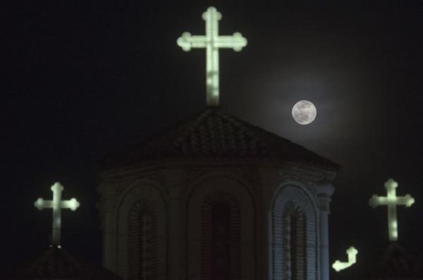 Theo phương Tây, mùa xuân bắt đầu vào ngày Xuân phân 20/03. Pha Trăng tròn hôm qua rơi vào đúng ngày Xuân phân, đánh dấu sự kết thúc của mùa đông bằng ánh trăng nhẹ dịu. Trong hình là Mặt Trăng đang tỏa sáng trên bầu trời một nhà thờ ở Skopje, quốc gia đông nam Châu u Macedonia. Ảnh: Robert Atanasovski/AFP.
