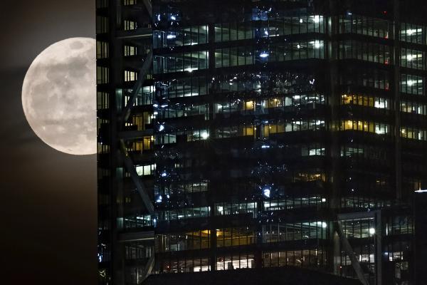 Lấp ló phía sau tòa nhà Trung tâm Thương mại Thế giới ở thành phố New York là Siêu Trăng cuối cùng của năm 2019. Ảnh: J. David Ake/AP.