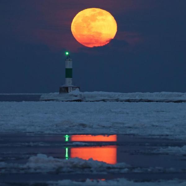 Lớp khí quyển dày nằm gần chân trời khiến hình ảnh Mặt Trăng bị méo mó. Đây là hình ảnh chụp Mặt Trăng lúc vừa mọc ở hồ Michigan tại thành phố cảng Milwaukee, tiểu bang Wisconsin, Hoa Kỳ. Ảnh: Mike De Sisti.