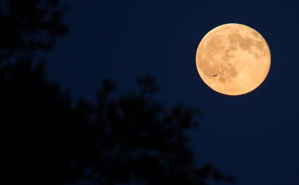 Một chiếc máy bay đang bay ngang qua phía trước Mặt Trăng trên bầu trời từ văn phòng của NASA ở Fort Myer Heights, Arlington, Virginia. Ảnh: NASA/Joel Kowsky.