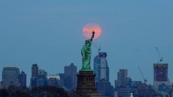 Trong góc ảnh này, bức tượng nổi tiếng Nữ thần Tự Do ở New York dường như đang quan sát Mặt Trăng mọc dần lên từ đường chân trời. Ảnh: Getty Images/Atilgan Ozdil/Anadolu Agency.