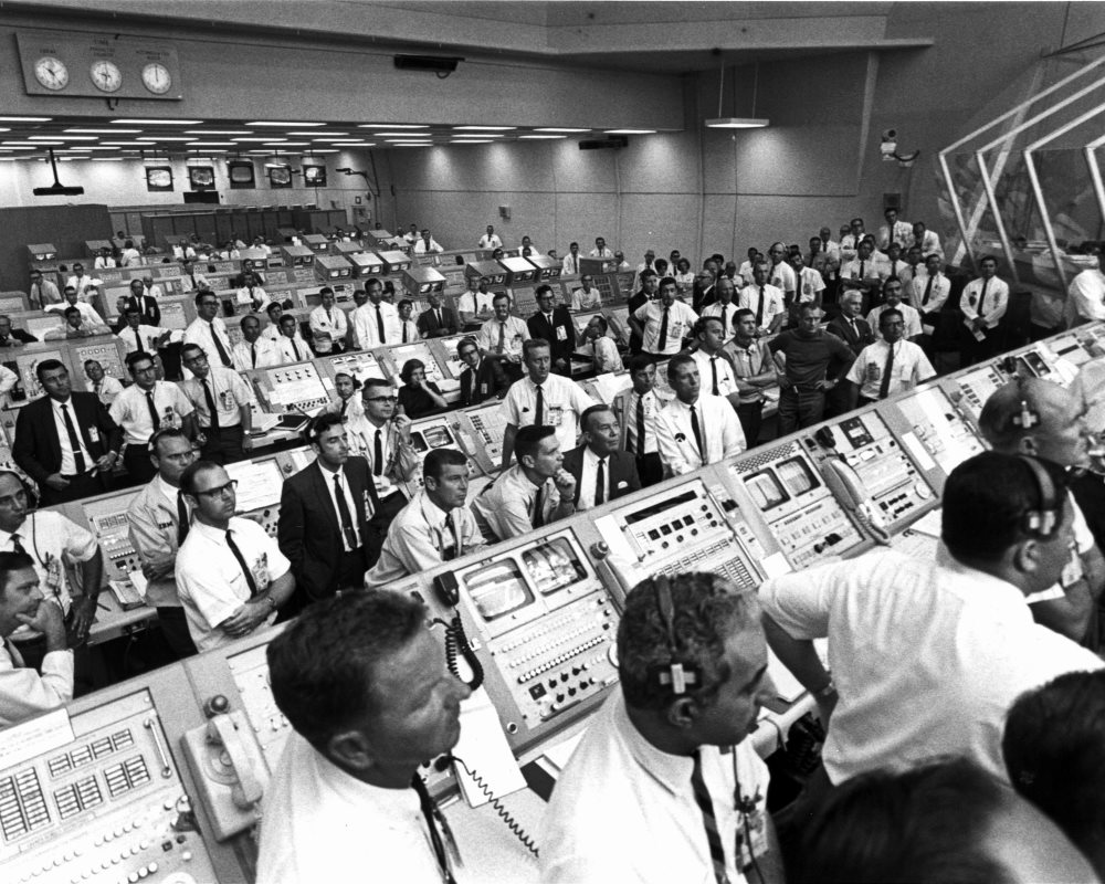 Nhân viên trong trung tâm điều khiển trạm mặt đất chăm chú theo dõi qua màn hình khi tên lửa Saturn V đang cất cánh từ Mũi Canaveral, Florida.