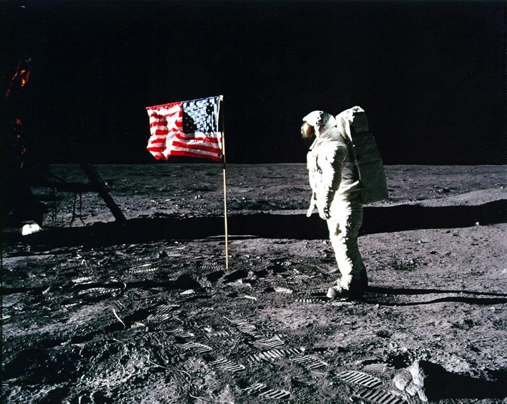 Phi hành gia Buzz Aldrin đứng bên cạnh quốc kỳ Mỹ. Hình ảnh được chụp bởi Neil Armstrong. Cột cờ này hiện vẫn còn được cắm trên Mặt Trăng.