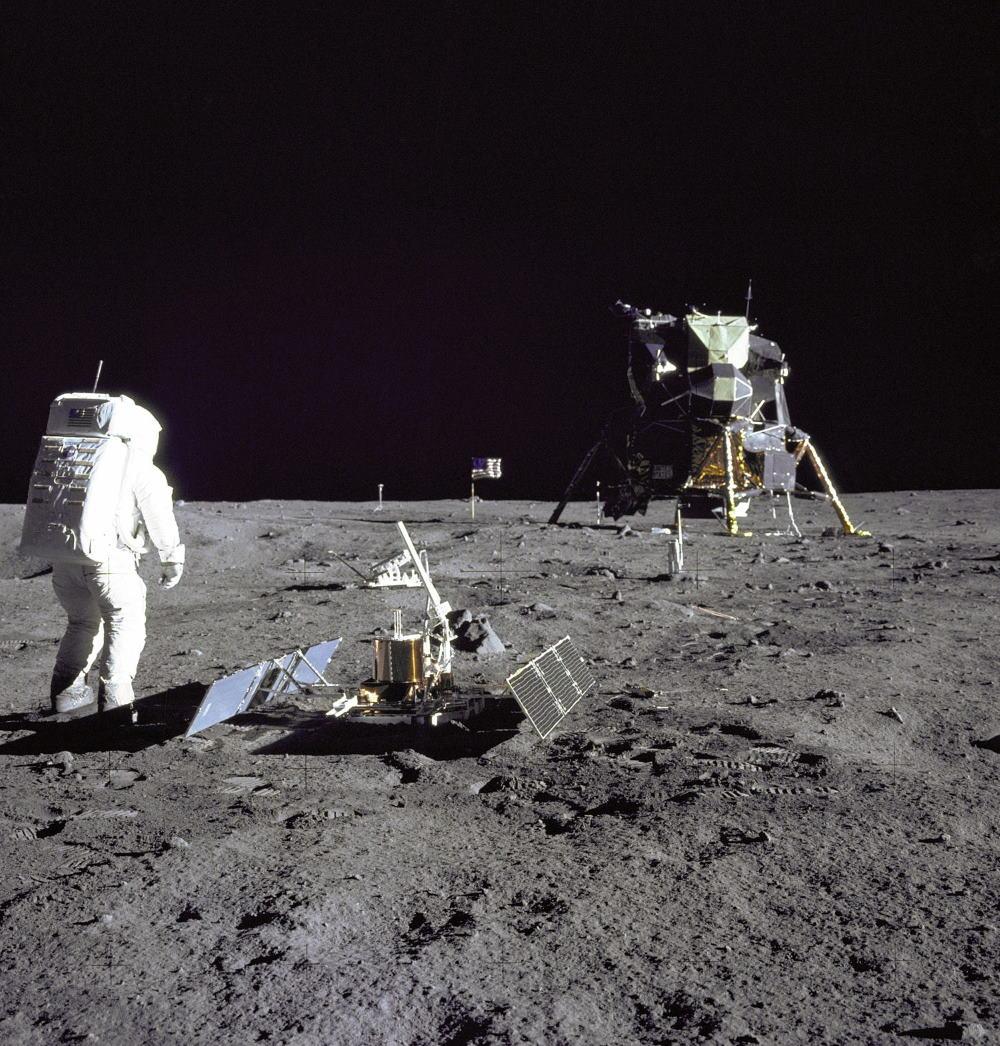 Buzz Aldrin đang thực hiện các thí nghiệm khoa học trên Mặt Trăng, ngay bên cạnh ông là bộ dụng cụ đo chấn động và xa hơn là thiết bị phản xạ laser.