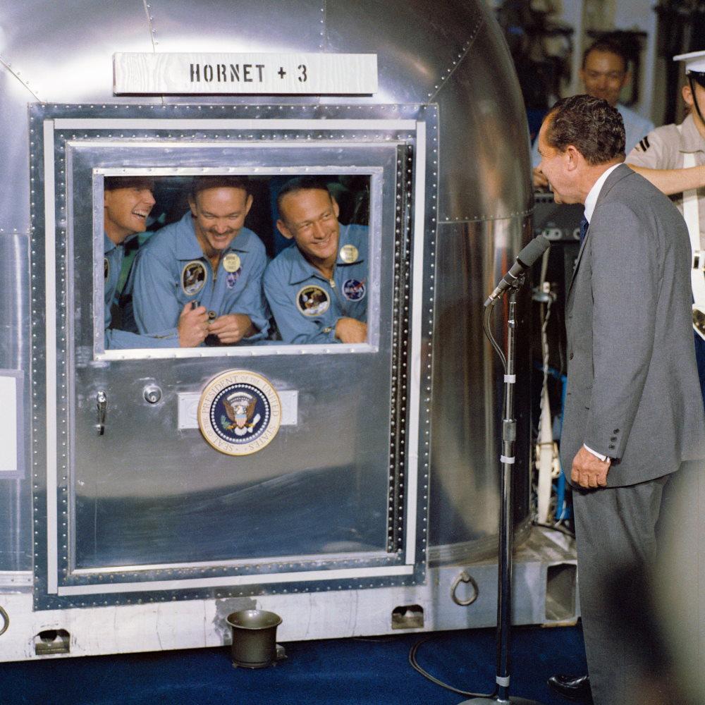Tổng thống Richard M. Nixon đích thân chào đón 3 phi hành gia của sứ mệnh Apollo 11 khi họ vẫn còn ở trong buồng cách ly khử trùng.