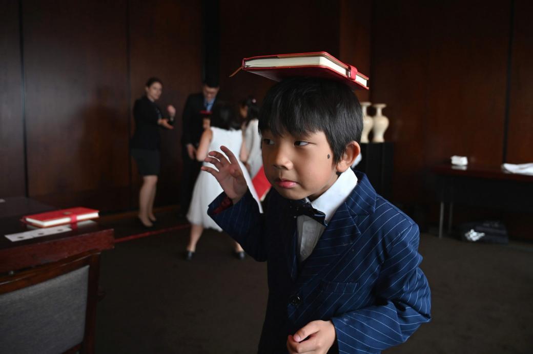 Alex Gao đang cố giữ cuốn sách trên đầu không bị rơi xuống. Cậu bé là một trong 7 học viên có mặt tại lớp học cuối tuần này được tổ chức tại một khách sạn 5 sao ở trung tâm thành phố Thượng Hải.