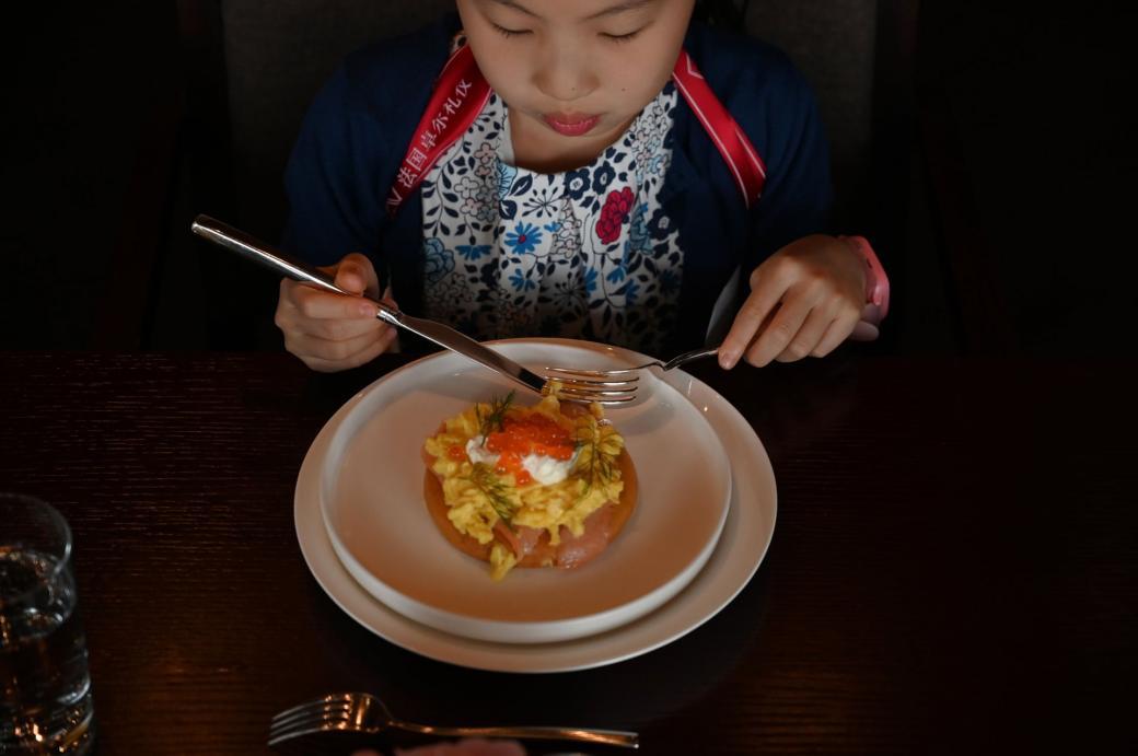 Danielle Liu học cách cầm dao nĩa để ăn uống các món Âu.