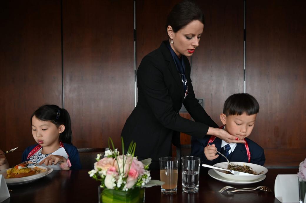 Những dải băng vải màu đỏ được quấn hờ sau cổ của những cô cậu bé là một cách để các em phải ăn uống thật nhẹ nhàng, vì nếu hành động mạnh dải băng sẽ bị rơi tuột.